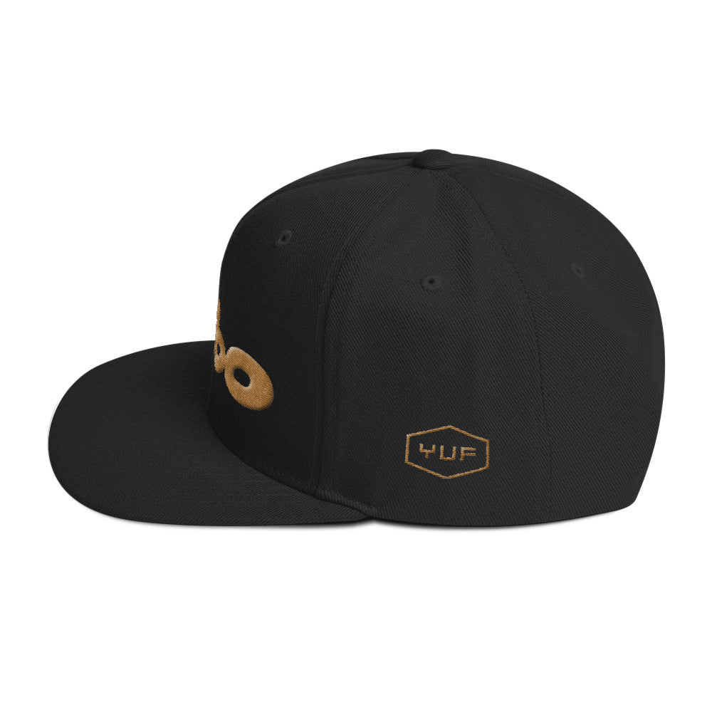 Side view of a black retro, classic snapback baseball cap with the sarcastic/ironic word BIMBO embroidered in a streetwise bubble / graffiti font for skateboarders, rappers, athletes, etc.