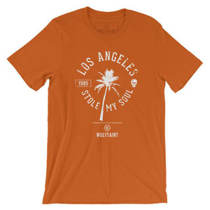 "A fashionable retro graphic t-shirt in orange, featuring a palm tree surrounded by the sarcastic words ""Los Angeles Stole My Soul"" with the year 1985 and a fun skull icon. From wolfsaint.net"