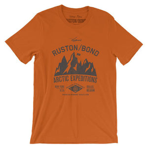 Orange classic, fashion, retro inspired t-shirt, with a fictional advertisement for an adventure company called Ruston/Bond Arctic Expeditions. It shows a mountain range and a helicopter, and lists the company locations in New York City and Ixelles, Belgium, and a Latin quote. Inspired by the films of Wes Anderson. From wolfsaint.net