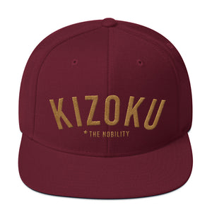 "A classic SnapBack cap in Maroon, with the Japanese word ""KIZOKU"" in raised gold embroidery, representing ""The Nobility"" —by fashion brand WOLFSAINT, from wolfsaint.net"