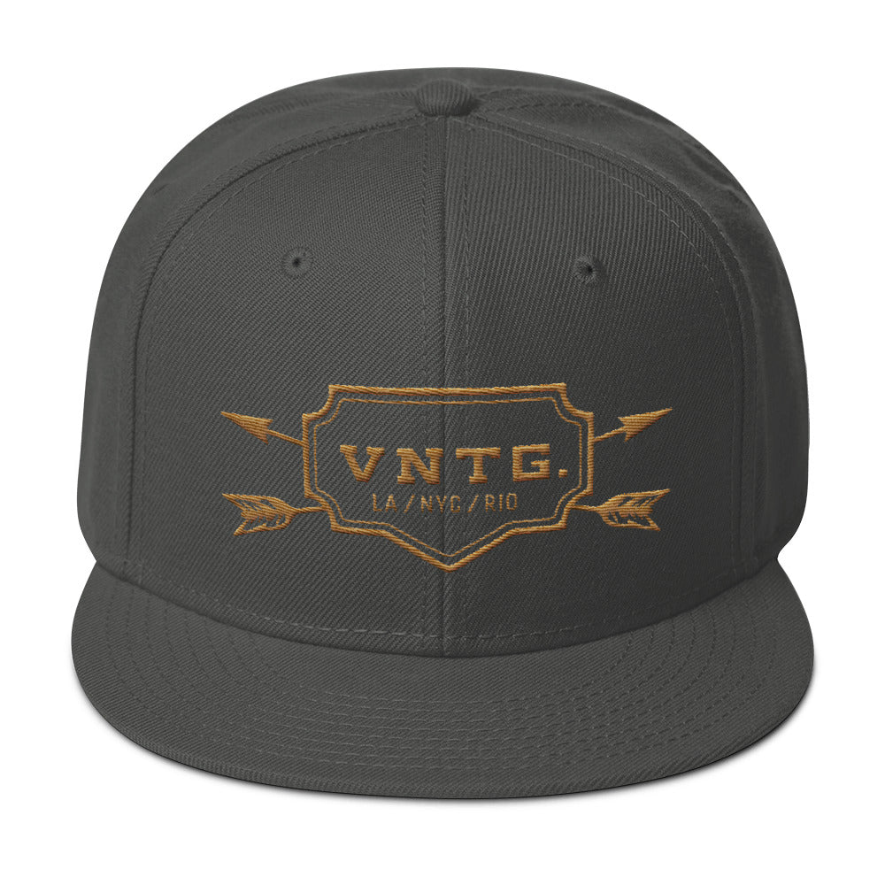 A classic SnapBack cap in Gray, featuring the VNTG. logo and it's cities (Los Angeles, New York City, Rio de Janeiro) within a shield, edged with crossing arrows. From wolfsaint.net