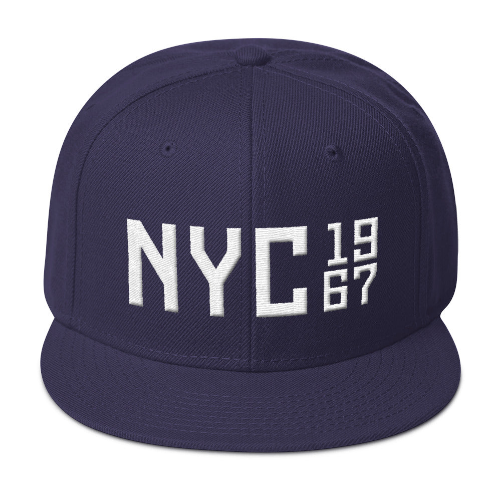 "A puff embroidery high-profile SnapBack cap in Navy Blue, with white thread of a large ""NYC"" (New York City) with the vintage year 1967 in a stack to the side. From wolfsaint.net"