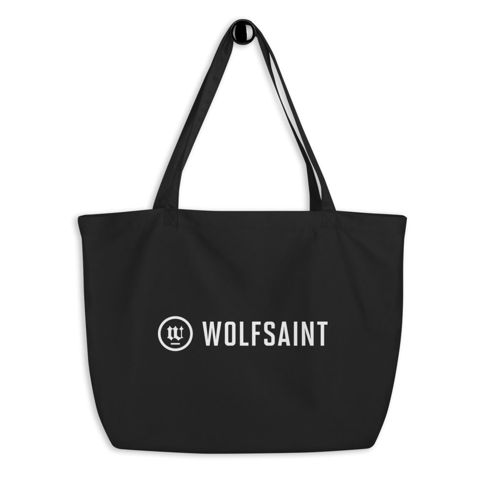 A large simple beach or city tote bag in black, with the WOLFSAINT gothic logo and crest printed in warm white. From Wolfsaint.net