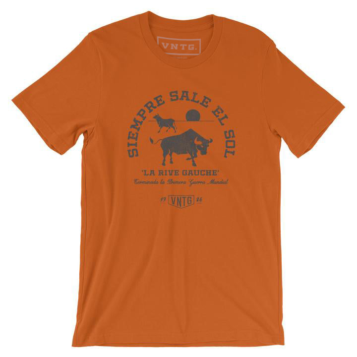 "A Classic fashion t-shirt celebrating Ernest Hemingway's novel ""THE SUN ALSO RISES,"" in its Spanish language translation. It reads ""SIEMORE SALE EL SOL"" around the image of two bulls, and ""la rice gauche."" By fashion brand VNTG., from wolfsaint.net"