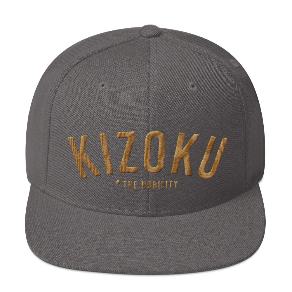 "A classic SnapBack cap in Gray, with the Japanese word ""KIZOKU"" in raised gold embroidery, representing ""The Nobility"" —by fashion brand WOLFSAINT, from wolfsaint.net"