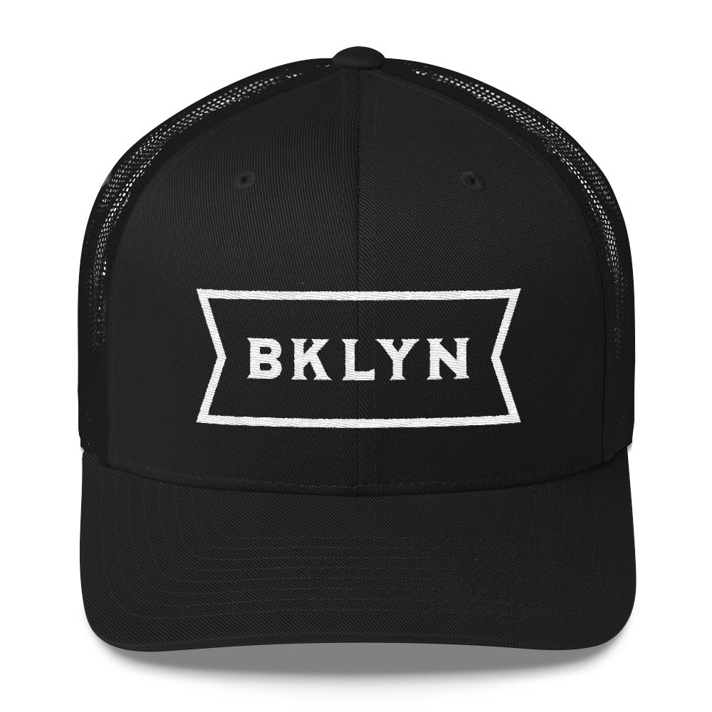 Black on black, mesh back classic trucker's cap, with a strong vintage abbreviated BROOKLYN typographic graphic. From wolfsaint.net