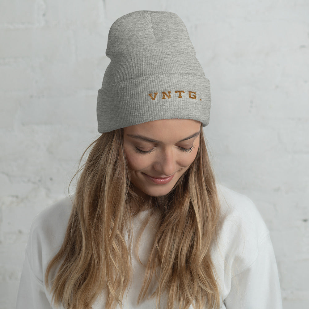 A smiling young woman wearing a stylish knit cap, with the brand logo VNTG. embroidered in gold thread. From wolfsaint.net