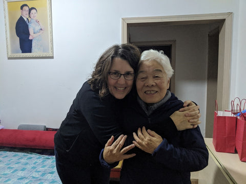 American Woman Hugging Older Chinese Woman in Chinese Home