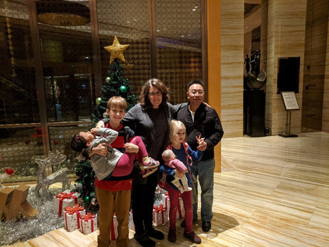 American Family with Adopted Chinese Daughter and Chinese Friend in Luxury Apartment Lobby in China