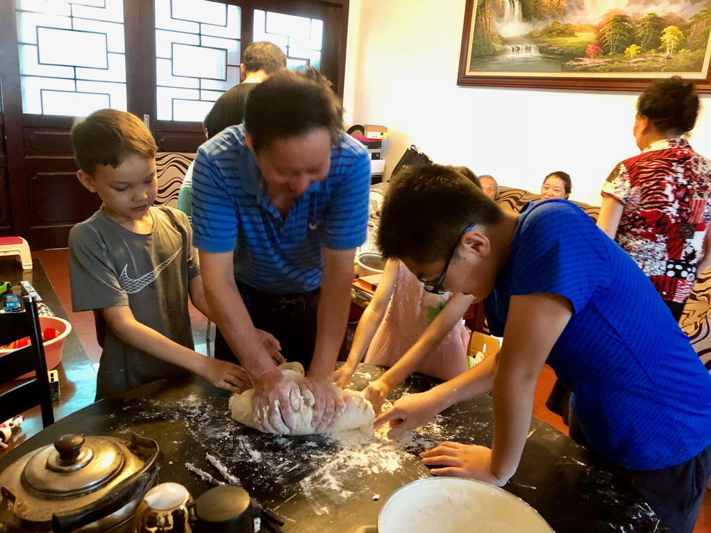 Boys helping elderly man make dumplings from scratch in Luzhou, China apartment