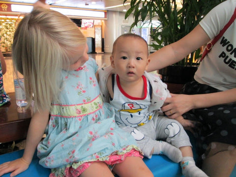 Kimberly's biological daughter Olive with a Chinese baby in Beijing airport