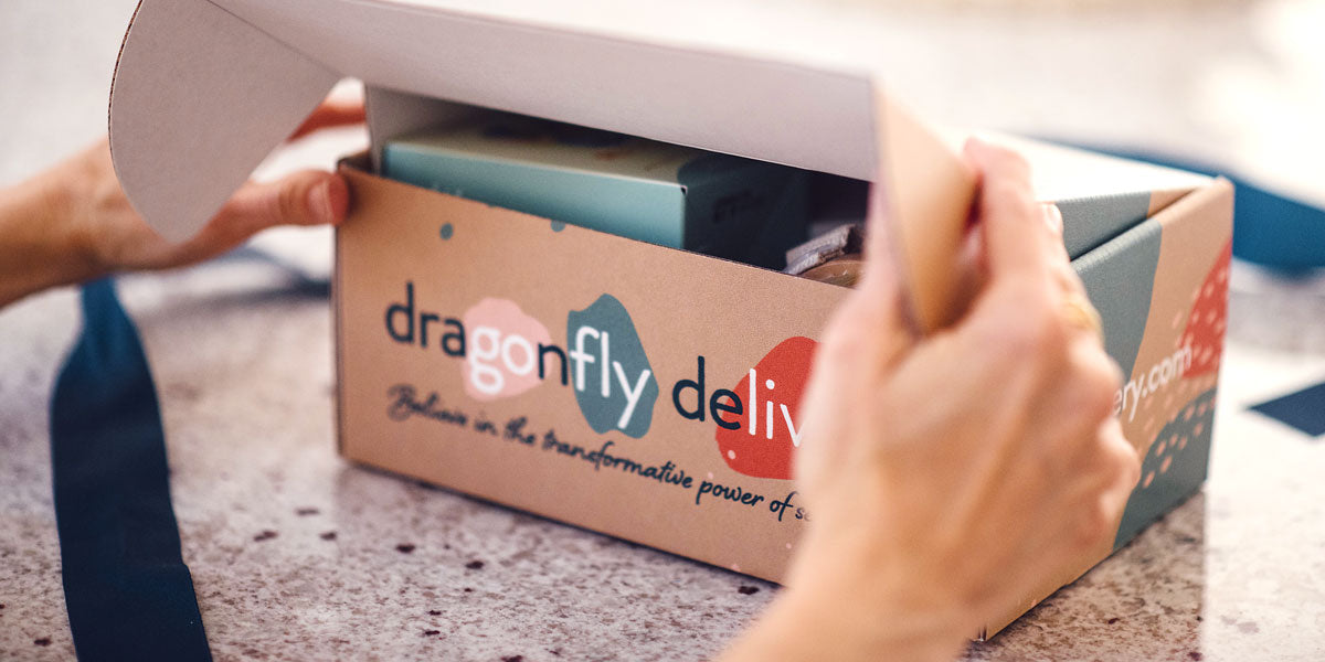 Hands opening Dragonfly Delivery box