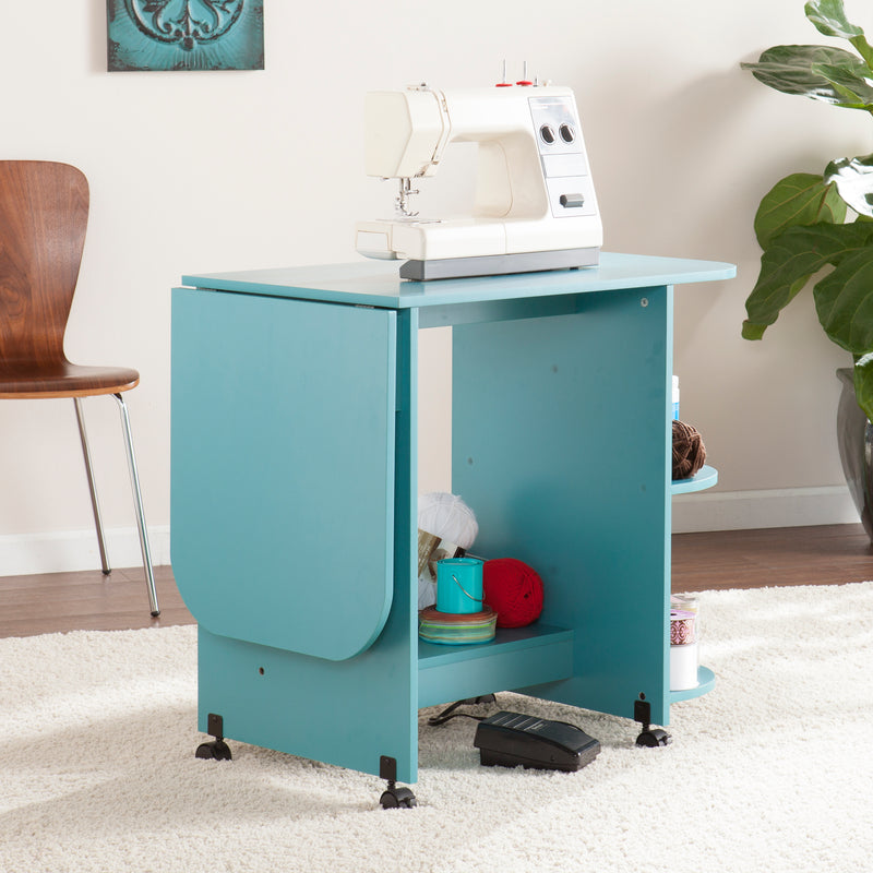 Turquoise Expandable Rolling Sewing Table/Craft Station - lifestyle photo, left angle, back view - arm folded down