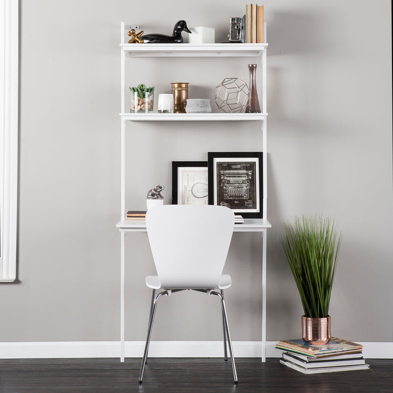 White Haeloen Wall Mount Desk - lifestyle photo - Desk against the wall next to a large plant. Decor on top two shelves and pens and books on desk top.