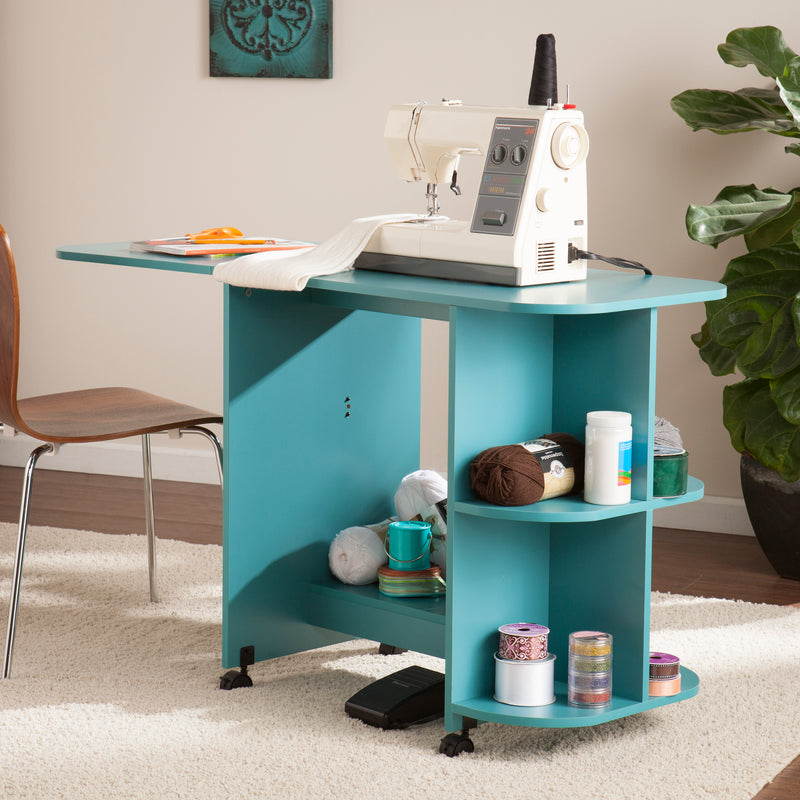 Turquoise Expandable Rolling Sewing Table/Craft Station - lifestyle photo with sewing machine on top and yarn on shelves