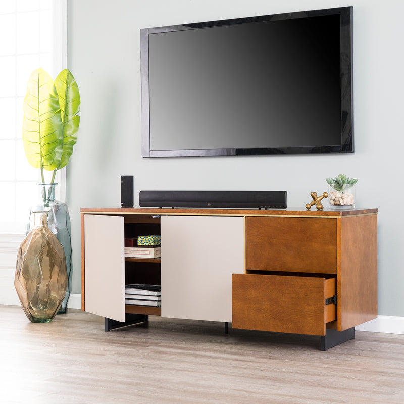 Midhurst Storage Media Stand lifestyle photo. Shown with TV mounted above, sound bar on top with decor. Media door opened with books inside and lower drawer pulled open.