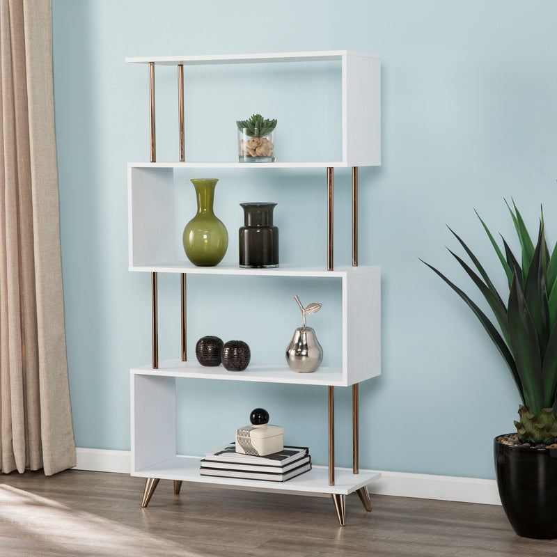 Beckerman Asymmetrical Etagere  is a zig zag bookcase with 5 open shelves. White finish with champagne gold accents. Shown against light blue wall with vases, plants, and books on shelves.