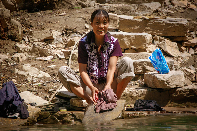 Chinese Woman Hand Washing Her Clothes on the River Rocks