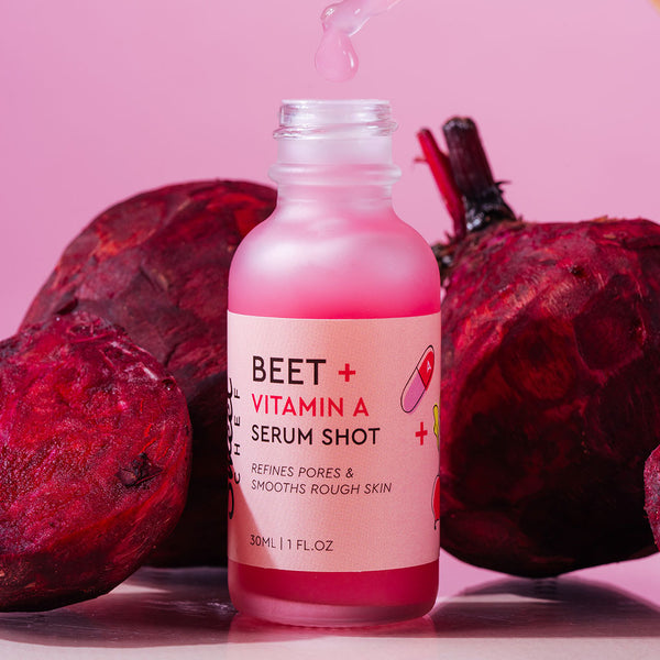 pink serum inside a clear glass bottle surrounded by beets