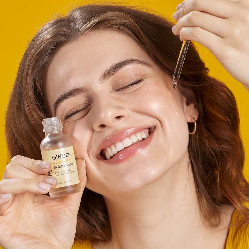 model smiling with joy as she applies serum to her face using a dropper