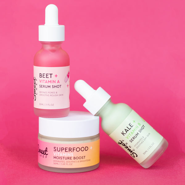 clear glass dropper bottle with pink serum paired with clear glass bottle with green serum balanced on a round container with a white top labeled superfood moisturizer