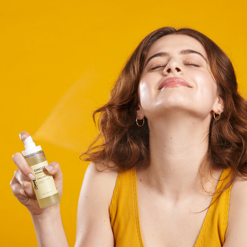 model in a yellow tank top smiling with joy as she sprays a mist across her face