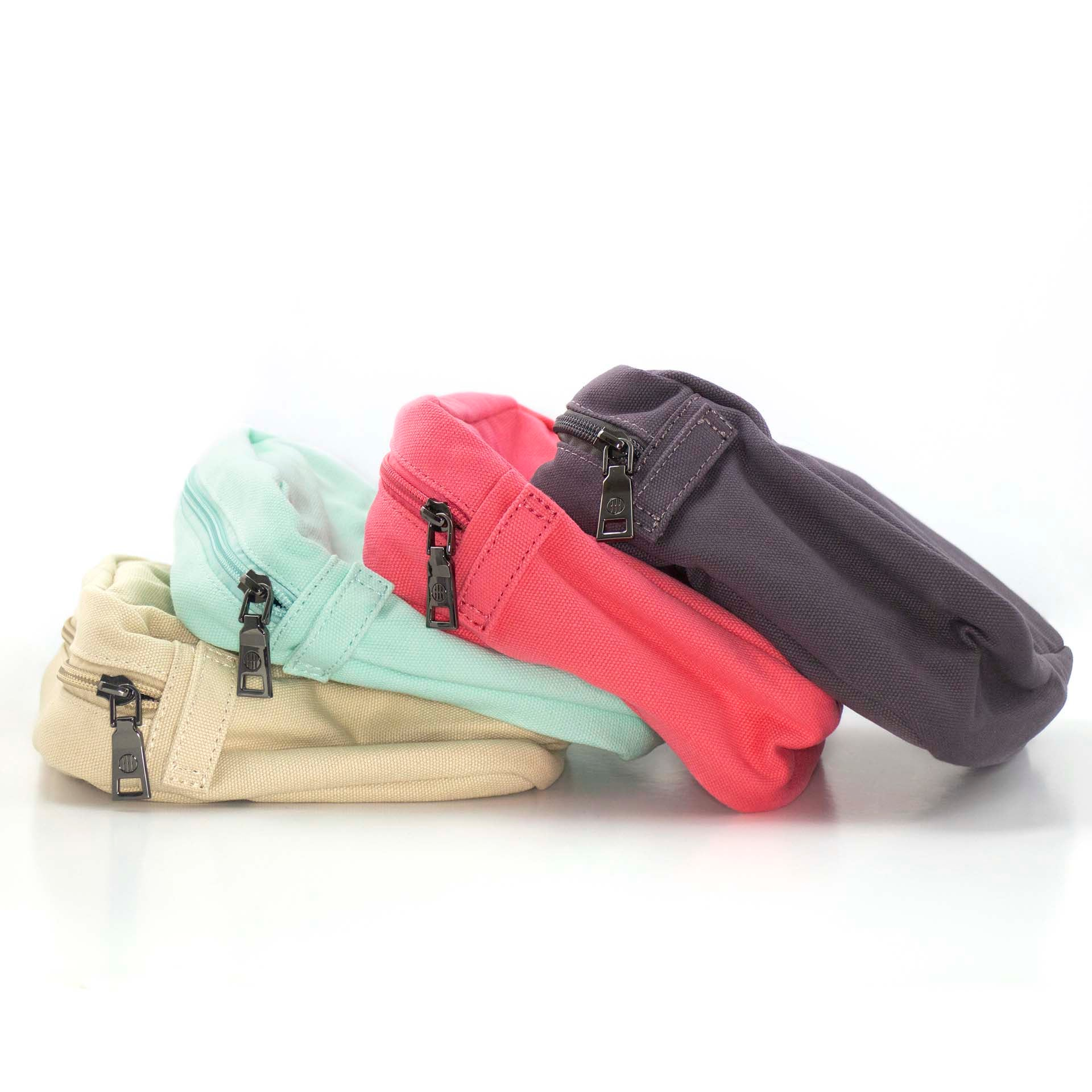 Four canvas bags, or pouches, with a zipper closure on the top. From left to right, the bags are shown in the colors beige, mint, coral, and charcoal.