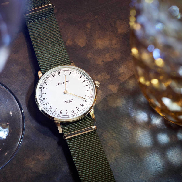24-hour watch with gold case and green NATO strap