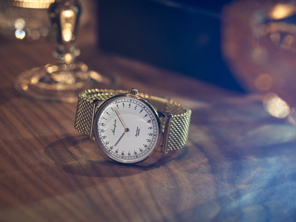 24-hour watch with gold case and gold mesh strap