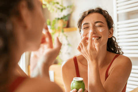 happy woman looking in mirror practicing self care and skin care