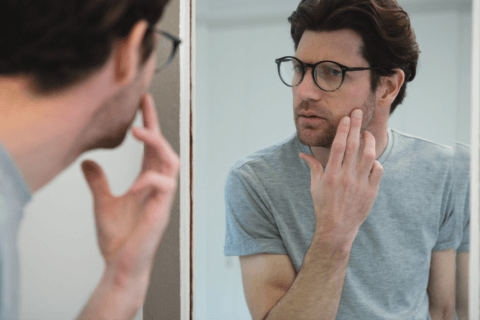 man checking face in mirror for red bumps