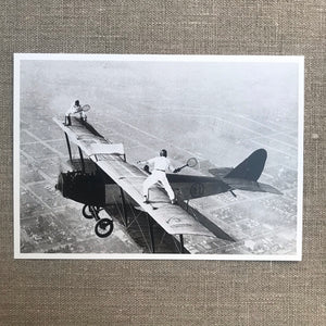 Ivan Unger and Gladys Roy playing tennis on wings of airplane in flight, c 1925
