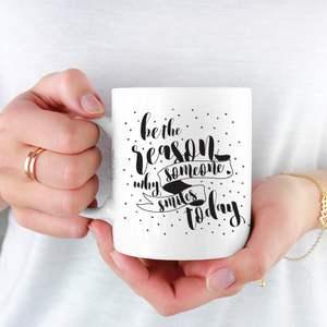 woman wearing white shirt holding white ceramic mug with black writing saying Be the reason why someone smiles today .