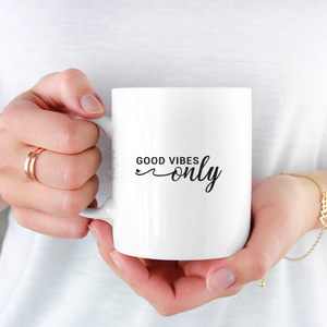 woman wearing white shirt holding white ceramic mug with black writing saying Good Vibes Only .