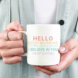 woman in jean jacket holding a white ceramic mug with unicorn color writing writing sayingHello. Good Morning. You're doing great. I believe in you. Keep going