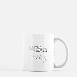 white ceramic mug with black writing saying In a world where you can be anything, be kind. plain white background