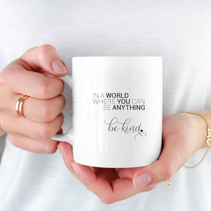woman wearing white shirt holding white ceramic mug with black writing saying In a world where you can be anything, be kind