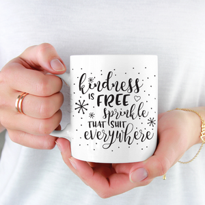 woman wearing white shirt holding white ceramic mug with black writing saying Kindness is free. Sprinkle that everywhere .
