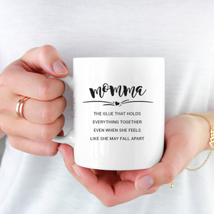 woman wearing white shirt holding white ceramic mug with black writing saying momma the glue that holds everything together even when she feels like she may fall apart.