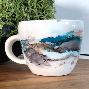Sea teal, black and copper alcohol ink hand-painted on 16oz stoneware coffee mug. Signed by the artist, Jaylin Knutson. left view
