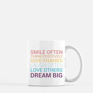 white ceramic mug with unicorn color writing saying Smile often. Think positively. Give thanks. Laugh often. Love others. Dream big. plain white background