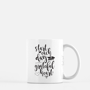 white ceramic mug with black writing saying Start each day with a grateful heart. plain white background