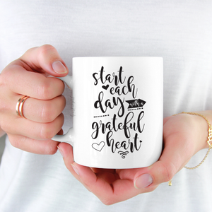 woman wearing white shirt holding white ceramic mug with black writing saying Start each day with a grateful heart