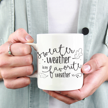 Load image into Gallery viewer, woman in jean jacket holding a white ceramic mug with black writing saying sweater weather is my favorite weather