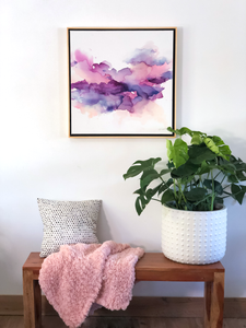 square painting in natural wood frame with plant in white pot and a bench with a cozy pink blanket and polka dot pillow