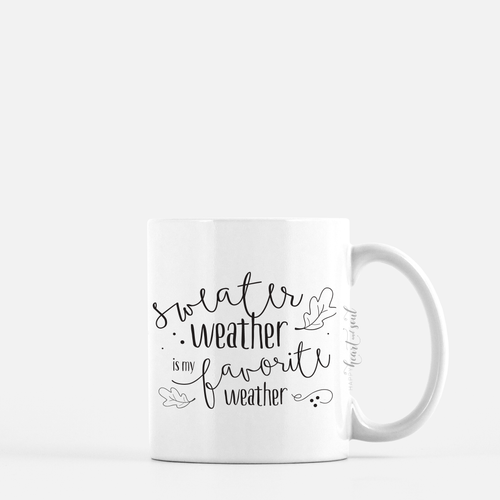 white ceramic mug with black writing saying sweater weather is my favorite weather . plain white background