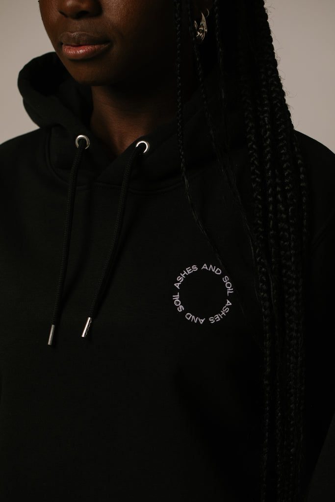 The unisex hoodie by ASHES AND SOIL is 85% combed ring-spun organic cotton and 15% recycled polyester. It has set-in sleeves, a hoodie with contrasting lining, a round cord of the same color, metal cord ends, and is roughened inside. The hoodie has a loose fit. For an oversize look, we recommend choosing one size bigger.