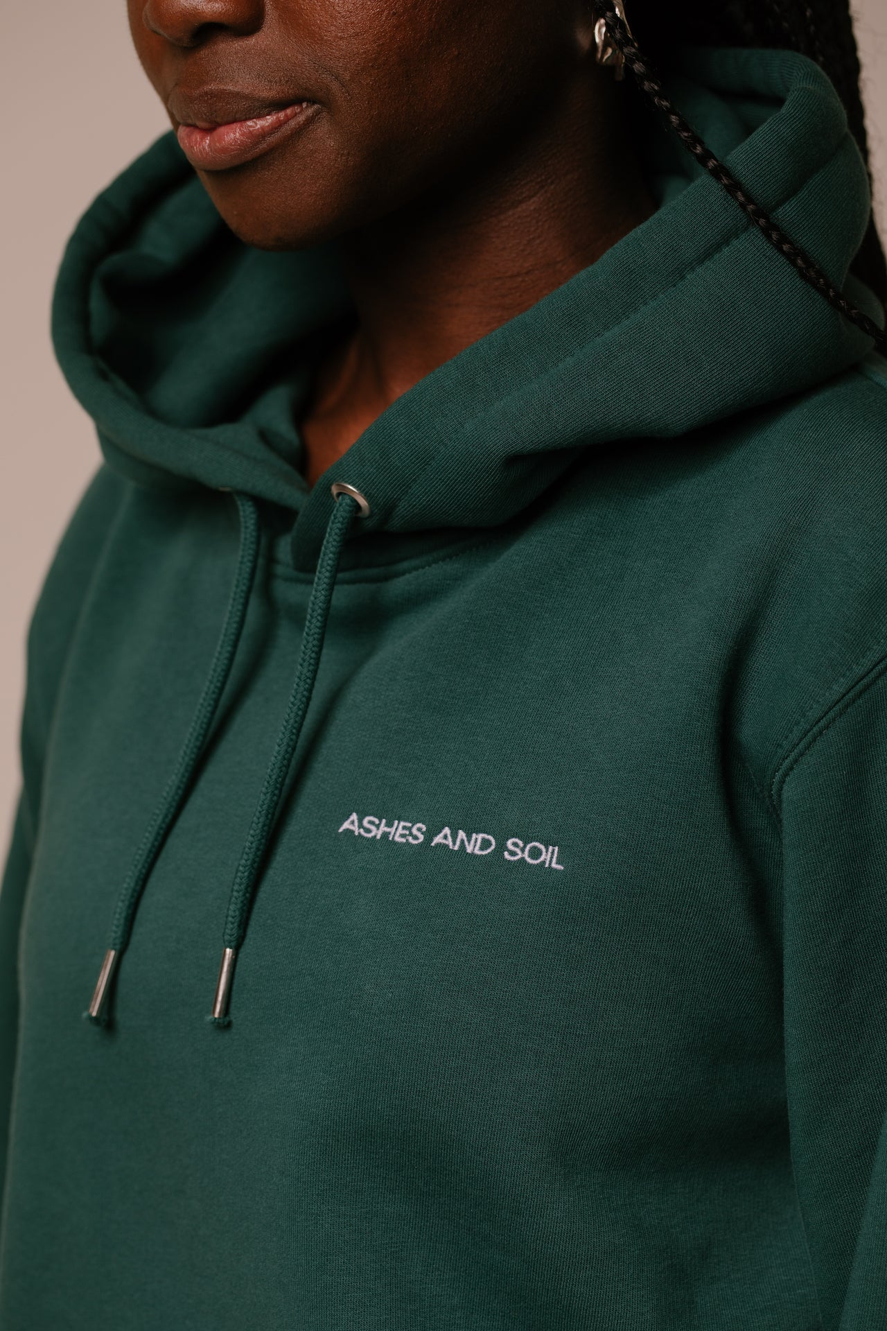 The unisex hoodie by ASHES AND SOIL is 85% combed ring-spun organic cotton and 15% recycled polyester. It has set-in sleeves, a hoodie with contrasting lining, a round cord of the same color, metal cord ends, and is roughened inside. The hoodie has a loose fit. For a complete oversize look, we recommend choosing one size bigger.