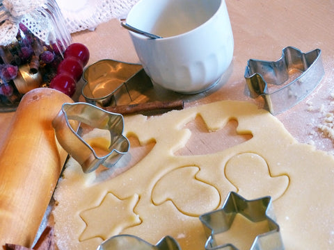 christmas cookies being cut with cookie cutters