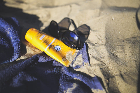 sunscreen and sunglasses on the beach